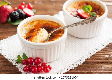 Delicious hazelnut-coffee creme brulee served in white ramekin with with fresh berries and mint leaves