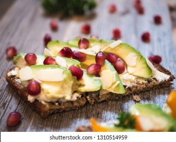 Delicious and healthy avocado toast with pomegranate, bell pepper and almond on rustic wooden board