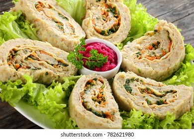 delicious healthy baked in oven minced white fish fillets roulade layered with carrots, cheese, greens on fresh salad leaves with horseradish sauce in center, view from above, close-up