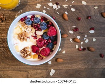 Delicious and healthy breakfast bowl with raspberry, blueberry, almond, pomegranate, walnuts and soy yogurt