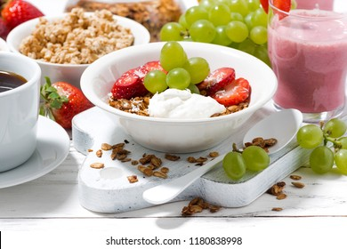 delicious and healthy breakfast with fruits, granola and milkshake on white table, horizontal