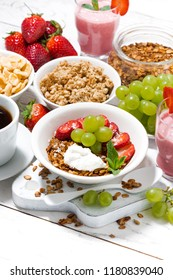 delicious and healthy breakfast with fruits, granola and milkshake on white table, vertical closeup
