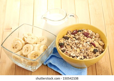 Delicious and healthy cereal in bowl with milk and bananas on table in room