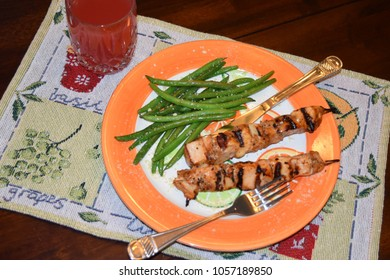Delicious and Healthy Chicken and Green Beans on a Citris Orange Plage with Silverware and an Crystal Glass of Red Punch
