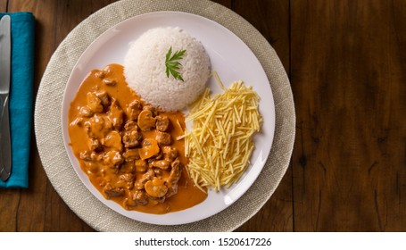 Delicious healthy food with meat strogonoff with rice and french fries on dish. View from the top.