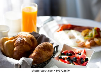 delicious healthy fruit bowl for breakfast with orange juice and pastries in the background, in-room dining at the hotel