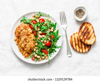 Delicious healthy lunch - baked chicken breast and white beans, arugula, cherry tomatoes salad on a light background, top view