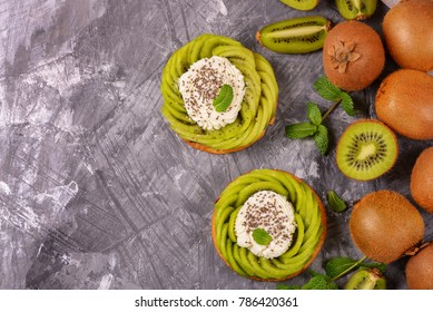 Delicious healthy tartlets filled with cheese cream and topped with kiwi slices in swirl and chia seeds. Healthy dessert concept.