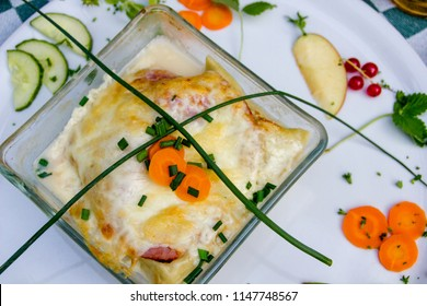 Delicious and healthy traditional south German  pasta dish so called Maultaschen baked in the ovent with cheese and cream, beautifully decorated with fruits and vegetables on a white dish.
