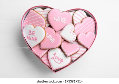 Delicious heart shaped cookies in box on white wooden table, top view. Valentine's Day
