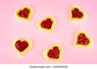 Delicious heart shaped cookies with marmelade in the middle, pink background