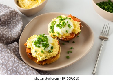 Delicious hearty breakfast, eggs Atlantic in a plate on a white background, round fried bun with salmon and eggs Benedict, hollandaise sauce and green onions