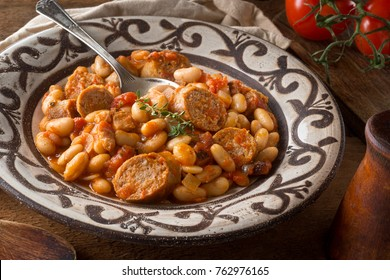 A delicious hearty cassoulet with artisinal sausage, tomato, bacon and white beans on a rustic tabletop.