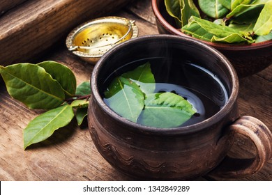 .Delicious herbal tea with bay leaf on wooden background