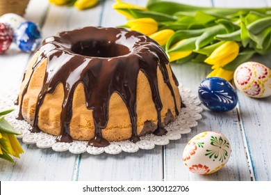 Delicious holiday slovak and czech cake babovka with chocolate glaze. Easter decorations - spring tulips and eggs.