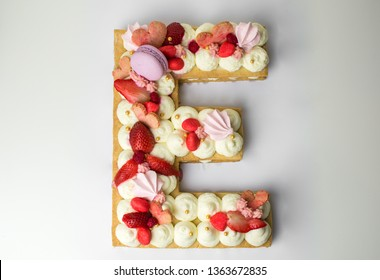 Delicious, homamade birthday cake in the form of an e letter with strawberry, macaroon and mascarpone cream decoration
