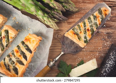 Delicious home made asparagus quiche with pecorino and bacon on rustic wooden background.  Top view.  Retro style toned.