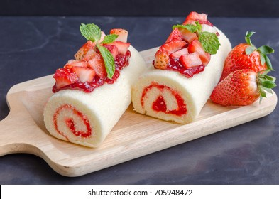 Delicious home made cake roll with strawberry marmalade jam in japanese style  on a wood plate with topping  fresh strawberry , strawberry marmalade jam and mint. Tasty dessert.
