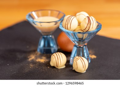 Delicious home made egg liqueur filled chocolate praline truffles displayed in a liqueur glass. The egg and liqueur representing the filling.