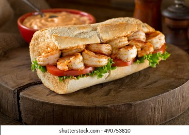 A delicious home made grilled shrimp Po Boy sandwich on baguette dressed with lettuce, tomato, and remoulade.