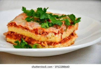 Delicious Home made keto diet  Lasagna bolognese  with  Lupin Flour, minced meat,tomato sauce and spinach  on a wooden rustic  background.Home made low carb italian meal