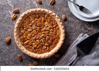A delicious home made pecan pie on a stone counter top.