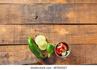 A delicious home made salsa pico de gallo with tomato, onion, lime, cilantro, and jalapeno pepper served on rustic wooden table. Selective Focus With Copy Space. Top View.