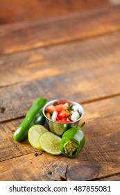 A delicious home made salsa pico de gallo with tomato, onion, lime, cilantro, and jalapeno pepper served on rustic wooden table. Selective Focus With Copy Space.