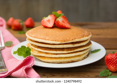 Delicious homemade american pancakes with fresh strawberry and honey. Pink napkin and wooden table.