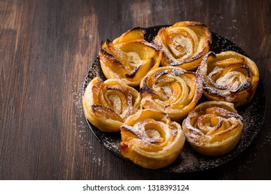 Delicious homemade apple pie roses on wooden background