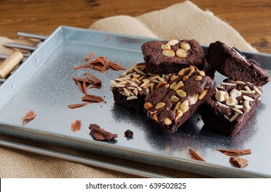Delicious homemade assorted chewy chocolate fudge brownies with mixed nuts (almond, cashew, macadamia) on baking tray - food photography