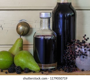 Delicious homemade autumn foraged elderberry and blackberry cordial in assorted glass bottles with juicy green pears and berries placed on farmhouse dresser