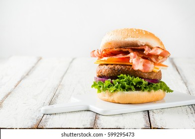 Delicious home-made bacon burger on white wooden background, copyspace