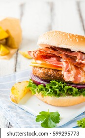 Delicious home-made bacon burger on white wooden background