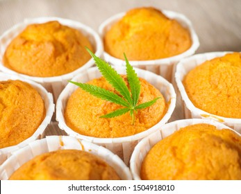Delicious homemade baked cinnamon muffins with marijuana leaf garnish. Cookies with cannabis and buds. Treatment of medical marijuana for use in food.