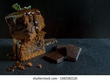 Delicious, homemade brownie with chocolate topping on dark background, food photography, Latvia