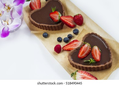 Delicious homemade chocolate tart with berries ornate with purple orchids
