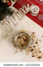Delicious homemade Christmas muesli in a glass jar. Photo of the granola is taken with beautiful Christmas decorations like a little three, red Christmas paper, etc. Warm white, brown, red and green.