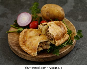 Delicious homemade Cornish pasties with beef, carrot, and potato on black background, opened up