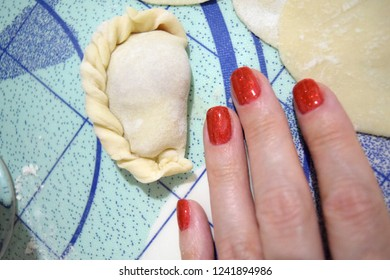 Delicious homemade dumplings and beautiful woman hand with red nails.
