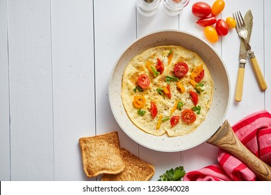 Delicious homemade egg omelette with tomatoes and parsley. Sprinkled with fresh pepper. Served with toasts. Top view with copy space.