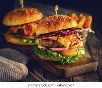Delicious homemade hamburger on wooden background. Rustic style. Retro toned.