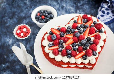 Delicious homemade heart shaped red velvet cake decorated with cream and fresh berries