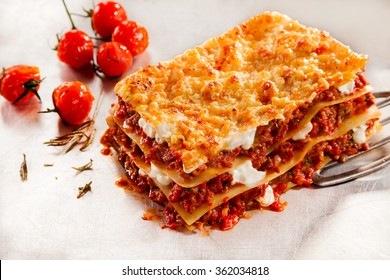 Delicious homemade Italian beef lasagne with roasted or oven-baked tomatoes on a serving spatula over a textured white background