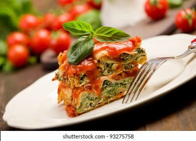 leckere hausgemachte Lasagne mit Ricotta-Käse und Spinat auf Holztisch