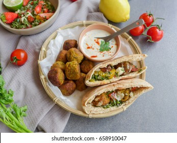 Delicious homemade middle eastern cuisine / Pita Bread with Falafel & Tabouleh Salad / Fresh ingredients,pita bread,chickpeas,tomatoes,strawberry,cilantro,feta cheese,mint leaves,and tahini sauce