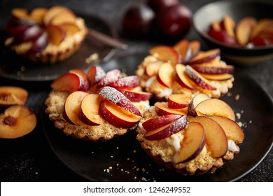 Delicious homemade mini tarts with fresh sliced plum fruit. Sprinkled with icing sugar. Placed on black ceramic plates with fresh pieces of plums on sides. Dark rusty background from top.
