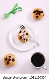Delicious homemade muffins and cup of coffee on white table.