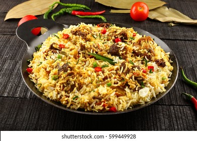 Delicious homemade mutton or lamb dum biriyani over wooden background,