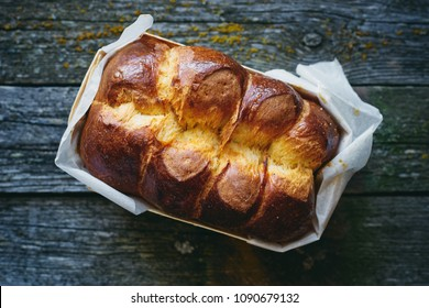 Delicious homemade organic fresh brioche bread on rustic wooden table top view
